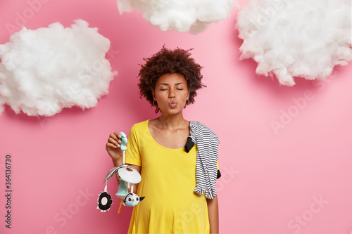 Fototapeta Adorable curly woman future mama with folded lips, dressed in comfy clothes, finds out gender of future baby, carries mobile and childs clothes stands against pink wall. Precious moments of parenthood obraz