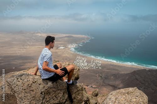 Cuadros en Lienzo Hombre joven contempla la playa de Famara desde la cima de una montaña