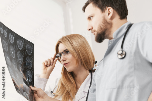 Young female doctor and handsome male nurse looking at x-ray exam #364155504