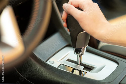 Slika na platnu Close up of woman driver holding her hand on automatic gear shift stick driving as car