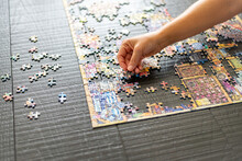 Woman's Hand Placing Puzzle Piece On A Partially Completed Puzzle On Wood Table