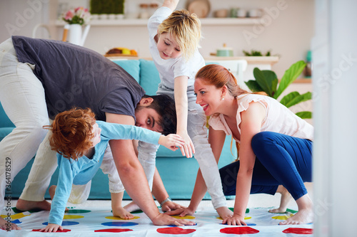 Valokuvatapetti cheerful family having fun, playing twister game at home