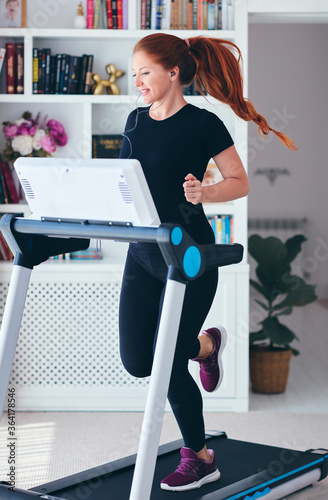 Fotografia happy woman exercising on a treadmill at home, healthy lifestyle