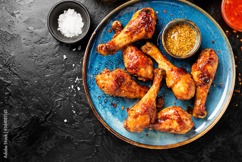 Fototapeta Roasted spicy chicken legs with mustard and chili sauce. obraz