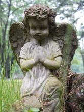 Closeup Of Weathered Statue Of Baby Cherub On Grave