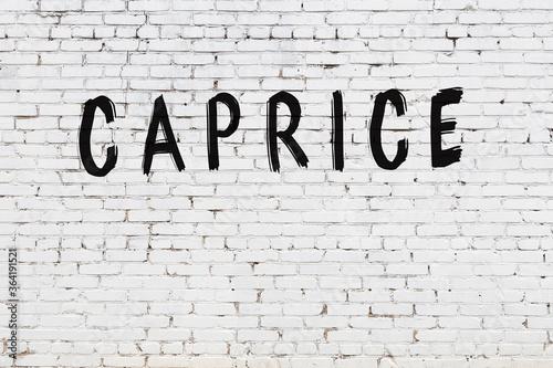 Fototapeta Inscription caprice painted on white brick wall
