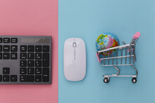 Global Supermarket. PC Keyboard And Shopping Trolley With Globe On Pink Blue Pastel Background. Top View
