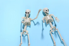 Two Fake Skeletons On Blue Bright Background. Halloween Decoration, Scary Theme. Flat Lay
