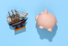 Piggy Bank And Ship On  Blue Sunny Bright Background. Travel Planning. Top View