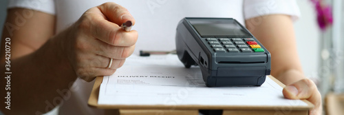Fotografia Close-up view of man holding cardboard box and payment terminal in hands
