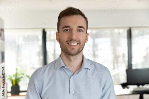 Fototapeta Profile picture of happy young Caucasian male employee worker look at camera pos