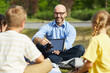 Portrait of bald male teacher pointing at tablet screen and smiling while talking to group of children during outdoor class in sunlight, copy space