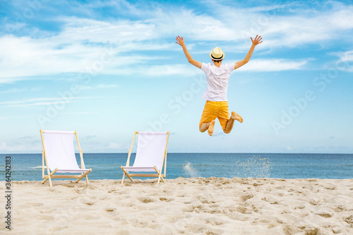 Valokuvatapetti Young man jumping on beach