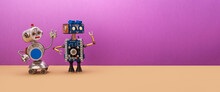 Two Robots Are Looking Away From Themselves. Creative Mechanical Toys, Steampunk Style. Copy Space For Text On A Purple-brown Background.