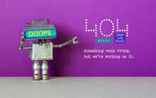 Oops 404 Error Page Not Found. Funny Robotic Toy Bot With Computer Monitor Head And Service Error Message. Purple Gray Background.