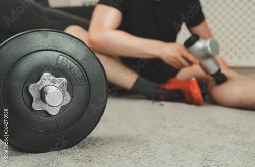 Fotografie, Obraz Man massaging leg with massage percussion device.