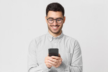 Young Man Wearing Gray Shirt And Glasses, Holding His Smartphone And Exchanging Messages With Friends With Smile, Isolated On Studio Background