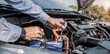 Auto mechanic using measuring equipment tool for fix checking car battery. Concepts of Old car repair service and insurance.