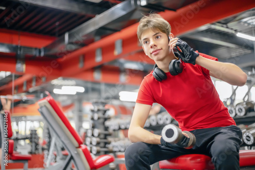 young man in a fitness club with a dumbbell in his hand is talking on the phone Canvas Print