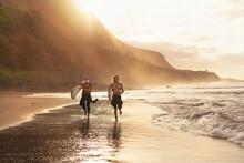 Happy Surfers Running On Beach...