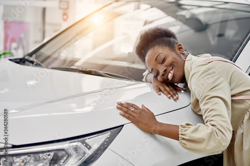 Fototapeta smiling black lady hugs her new auto in cars showroom. young woman fulfill her dream, lies on car obraz