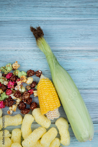 Valokuva top view of cut corn and uncooked corn with skittles popcorn and corn pop cereal
