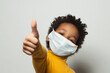 canvas print picture - Happy African American black kid in medical protective face mask showing thumb up on white