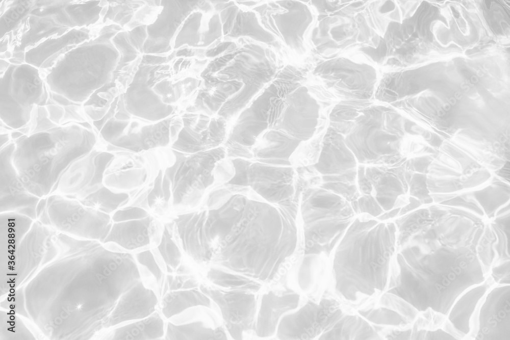 Closeup of desaturated transparent clear calm water surface texture with splashes and bubbles. Trendy abstract nature background. White-grey water waves in sunlight