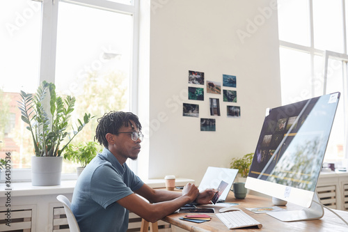 Obraz Portrait of young African-American photographer using computer at desk in home office with photo editing software on screen, copy space - fototapety do salonu