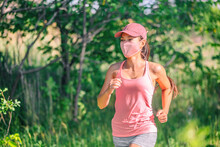 Mask Wearing During Exersice For COVID-19 Protection Asian Girl Running Outside With Face Covering While Exercising Jogging On Run Sport Workout In Summer Park Nature. Pink Mask, Cap, Tank Top.