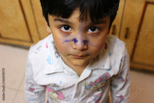 Foto Cute little Indian boy with blue ink spread on his face