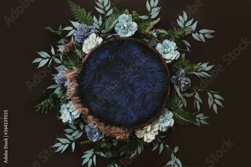 Photo Newborn digital background - brown wooden bowl with green leaves wreath,  teal flowers and blue faux fur