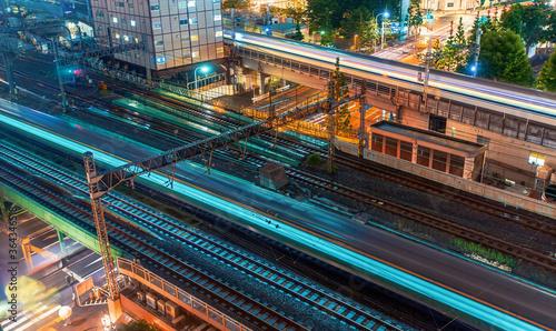 Trains speed through Tokyo, Japan at night