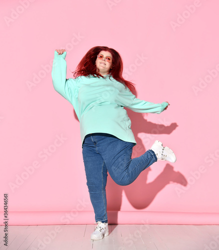 Photo Pretty plump woman with ginger hair in jeans, cosy hoodie and sneakers having mu