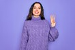 Young beautiful woman wearing casual turtleneck sweater standing over purple background showing and pointing up with fingers number three while smiling confident and happy.