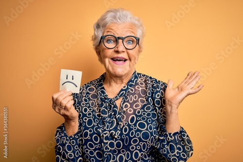 Senior beautiful grey-haired woman holding reminder paper with sad emotion face Fototapeta