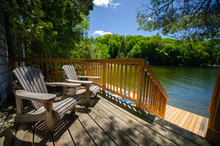 Adirondack Chairs Sitting On A Cottage Wooden Deck Facing A Calm Lake During A Summer Day In Muskoka, Ontario Canada.