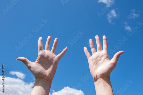 Photo Close-up of female hands, empty open palms on a background of blue sky