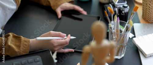 Female designer drawing on digital tablet with stylus pen on worktable with pain Canvas Print