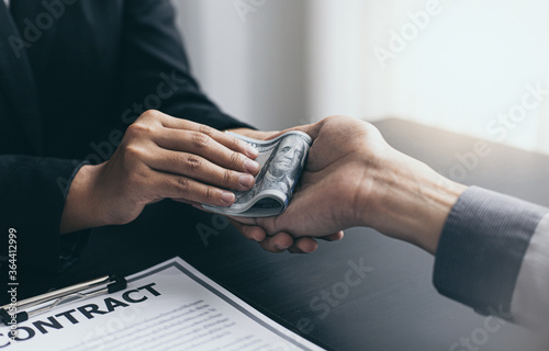 Cuadros en Lienzo Young man's hand received a dollar from the woman's hand in the office to bribe