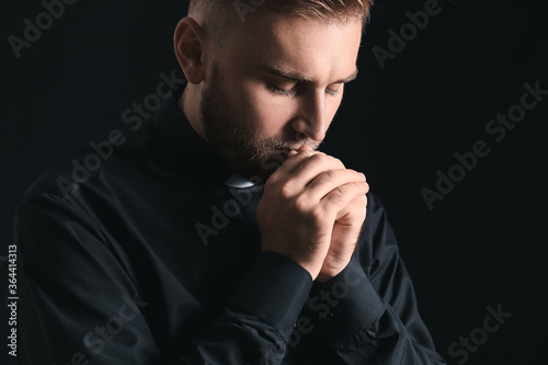Fotografie, Obraz Young priest praying to God on dark background