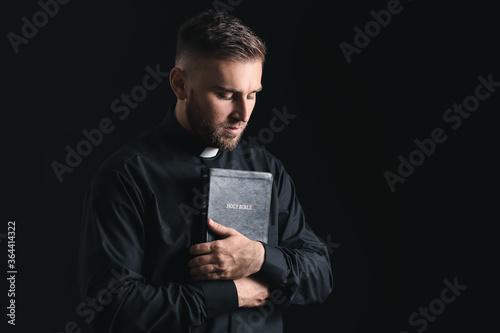 Obraz na plátně Young priest praying to God on dark background