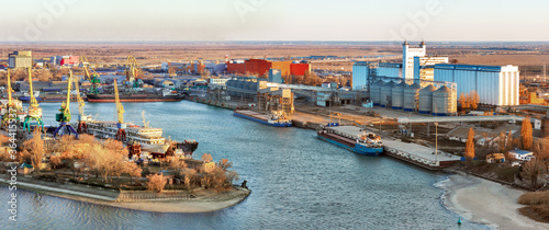 Cuadros en Lienzo The panoramic view the river harbor with the big industrial building of grain elevator and  a cargo berth for loading grain onto bulk-carriers