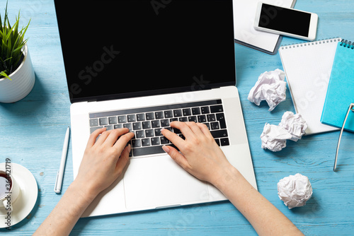 Valokuvatapetti Freelancer sitting at desk and working with laptop