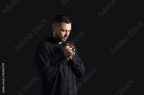 Obraz na plátne Handsome praying priest on dark background
