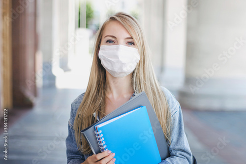 Tablou Canvas Caucasian student girl wearing a medical mask holds exercise book in her hands a