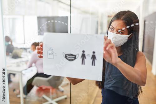 Business Frau mit Alltagsmaske befestigt Aushang