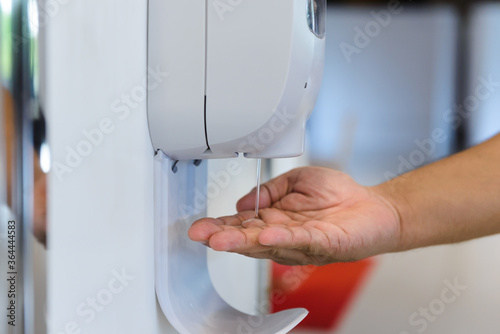 Obraz na plátně close-up hand male under automatic alcohol gel dispenser for cleaning hand and clear bacteria for stop Covid 19 virus outbreak