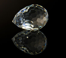 Large Faceted Crystal On A Black Reflective Surface
