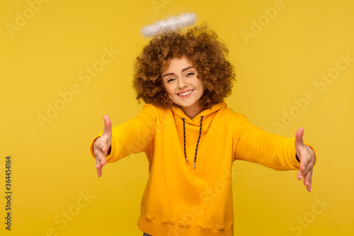 Portrait of kind-hearted generous curly-haired hipster woman with saint nimbus raising hands to embrace, giving free hugs and smiling with love Tableau sur Toile
